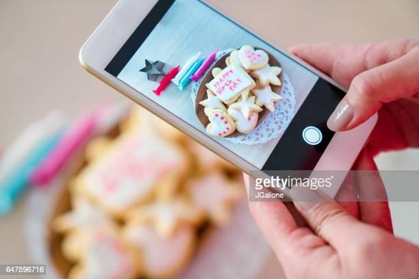 女性がスマート フォンを使用して新鮮な装飾が施されたクッキーの写真を撮る