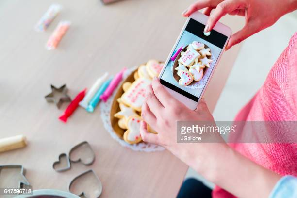 woman using a smartphone to take a photo of freshly decorated cookies - decorating a cake stock pictures, royalty-free photos & images