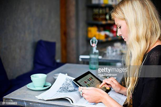 woman using a tablet computer in a cafe - leanincollection stock pictures, royalty-free photos & images