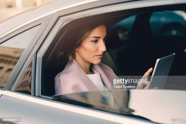 Woman using a tablet in a car