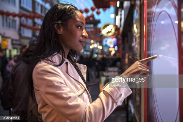 woman using a touch screen finding informations online in london city streets - touch screen stock pictures, royalty-free photos & images