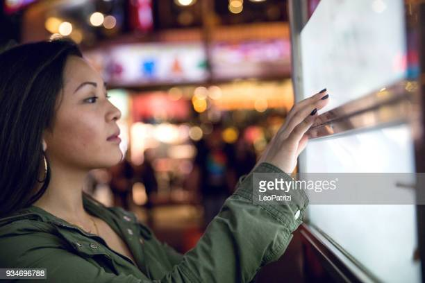 woman using a touch screen finding informations online in london city streets - touch sensitive stock pictures, royalty-free photos & images