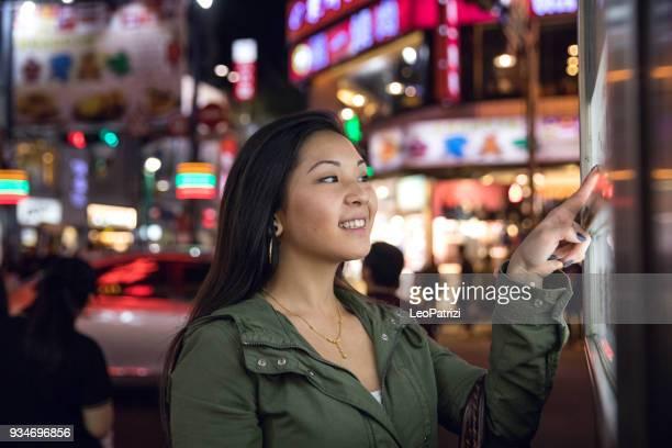ロンドンの街のオンライン情報を見つけるタッチ スクリーンをしている女の人