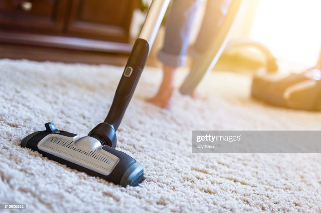 Woman using a vacuum cleaner while cleaning carpet in the house. : Stock Photo