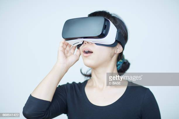 woman using a virtual reality headset - virtual reality simulator stock photos and pictures