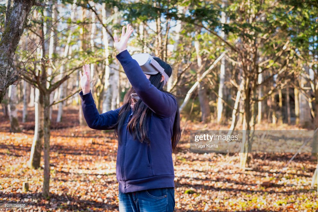 Woman Using a VR Headset in a Forest in Autumn : ストックフォト
