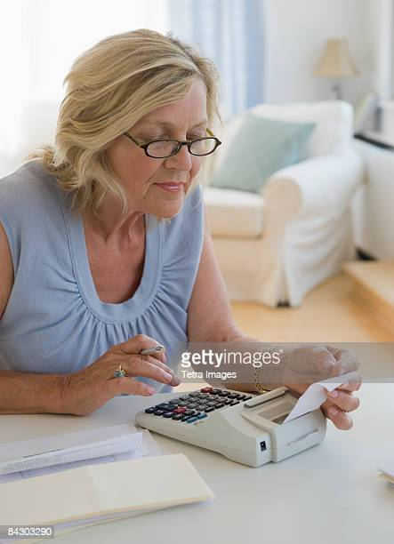 Woman using adding machine at home
