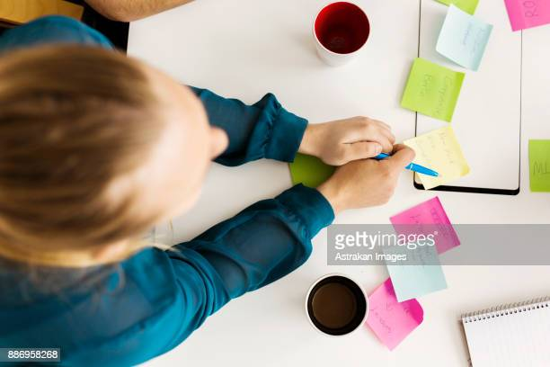 Woman using adhesive notes during business meeting