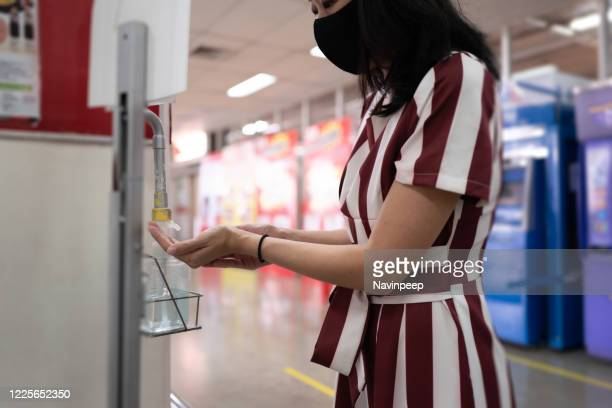 woman using alcohol gel to disinfect hand at department store entrance - antiseptic stock pictures, royalty-free photos & images