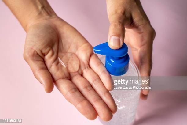 woman using alcohol-based hand sanitizer - lavage des mains photos et images de collection
