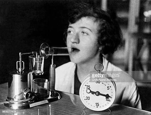 A woman using an electric inhaling apparatus which produces a medicated fog used in the treatment of colds and influenza circa 1929
