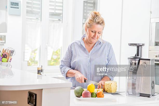 woman using an electric juicer in her kitchen - fat blonde women stock photos and pictures