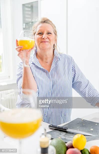 woman using an electric juicer in her kitchen - blond mollig frau stock-fotos und bilder