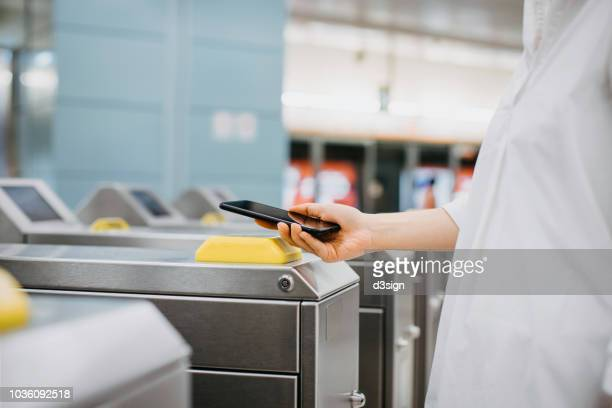 woman using app device on smartphone to pay for subway ride - commuter stock pictures, royalty-free photos & images