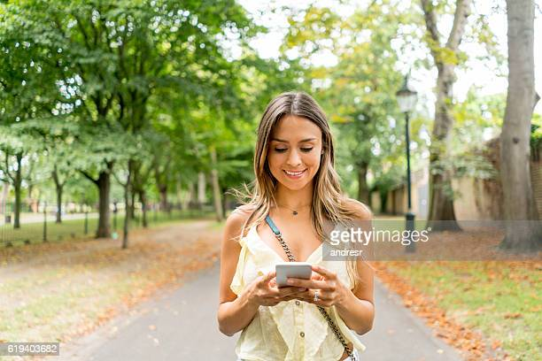 Woman using app on a cell phone at the park
