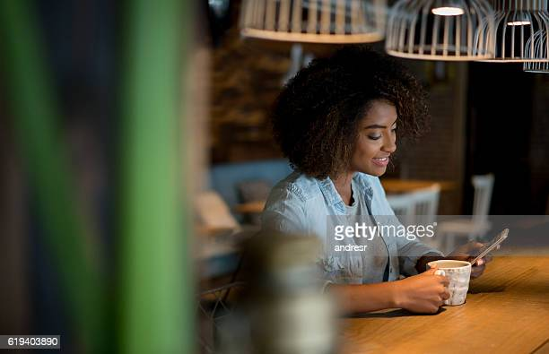 Woman using app on her cell phoen at a cafe