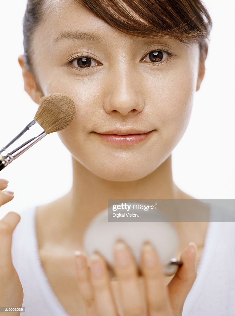 Woman Using Applying Powder to Her Face With a Brush : Stock Photo