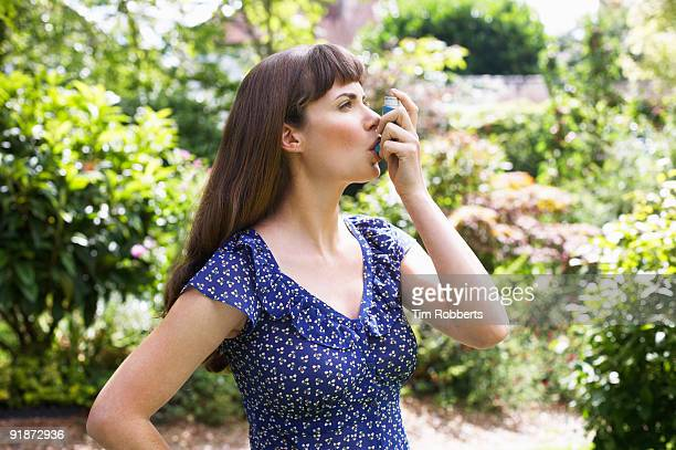 Woman using Asthma inhaler in garden