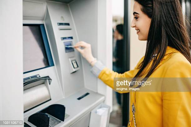 woman using atm machine - atm stock pictures, royalty-free photos & images