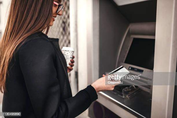 woman using atm machine - bank account stock pictures, royalty-free photos & images