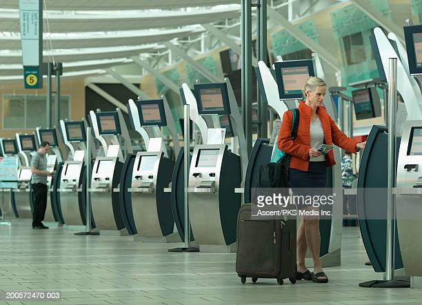 Woman using automated airport check in