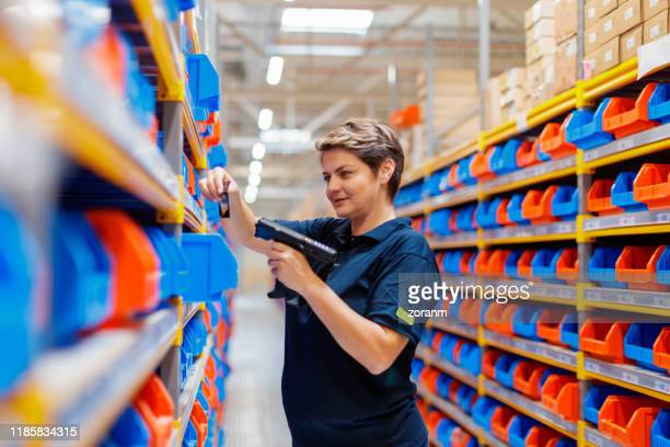 woman using barcode reader at warehouse - industrial storage bins stock pictures, royalty-free photos & images