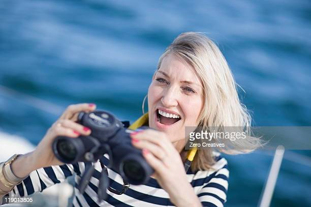 Femme à l'aide de jumelles dans le bateau