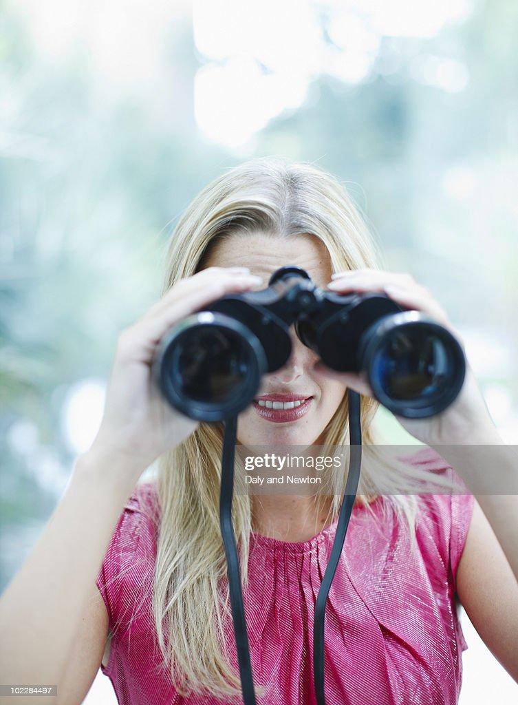 Woman using binoculars : Stock Photo