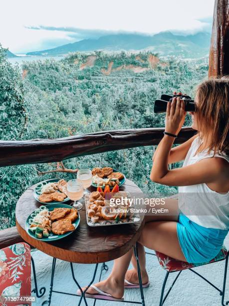 woman using binoculars while sitting by food on table - dominica stock pictures, royalty-free photos & images