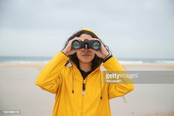 woman using binoculars while standing at beach - binoculars stock pictures, royalty-free photos & images