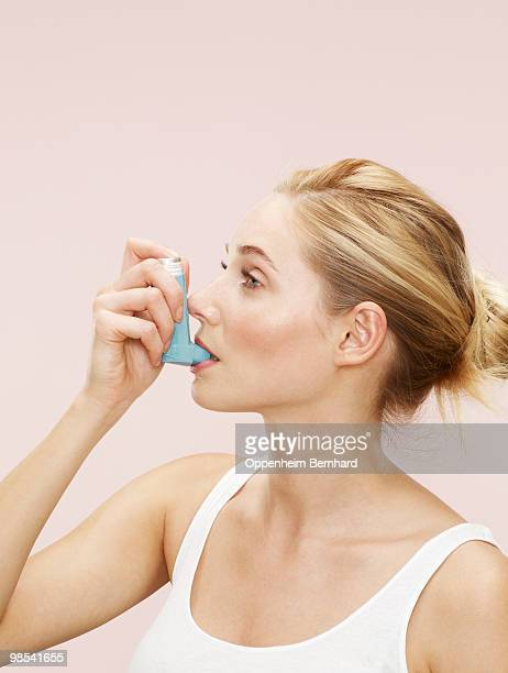 woman using blue inhaler - asthma stock pictures, royalty-free photos & images