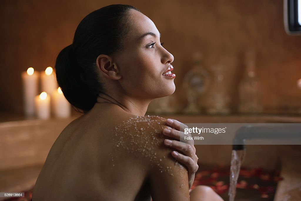 Woman using body scrub in bath : Bildbanksbilder