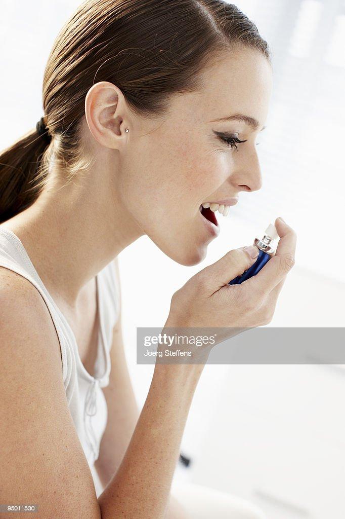 Woman using breath spray : Stock Photo
