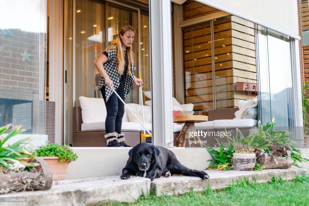 Woman using broom to clean up backyard patio after party : Stock Photo