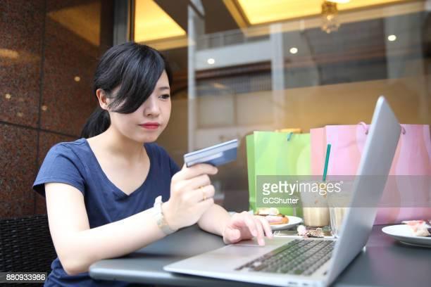 オープン カフェでは、インターネットから何かを購入するキャッシュレス支払いをしている女の人