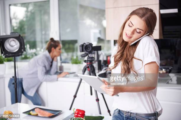 woman using cell phone and tablet in kitchen - video call stock-fotos und bilder