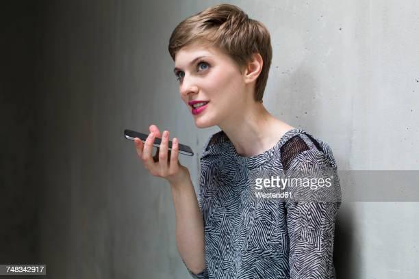 woman using cell phone at concrete wall - voz - fotografias e filmes do acervo
