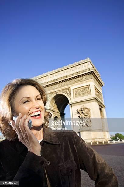 Woman using cell phone by Arc de Triomphe, Paris