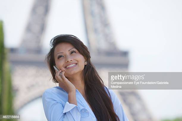 "woman using cell phone by eiffel tower - ""compassionate eye"" stock-fotos und bilder"