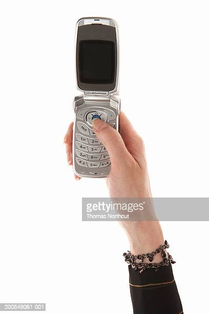 Woman using cell phone, close-up of hand