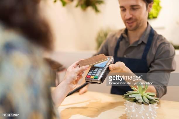 woman using cell phone contactless payment in flower shop - trabalho comercial - fotografias e filmes do acervo