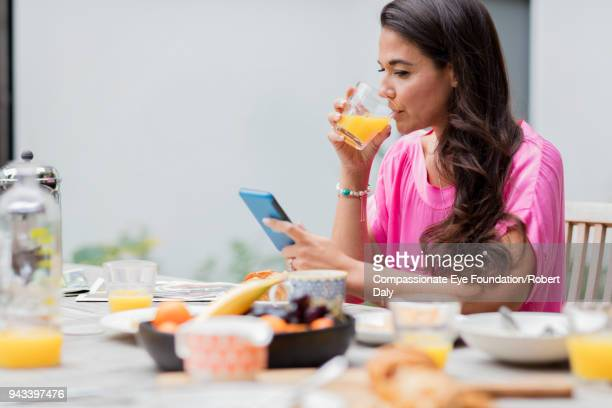 Woman using cell phone having breakfast on patio