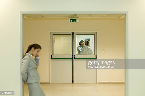 Woman using cell phone in hospital waiting room, doctor and patient in background