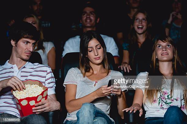 woman using cell phone in movie theater, man looking over with annoyed expression - irritation stock pictures, royalty-free photos & images
