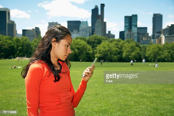 woman using cell phone in park - ニューヨーク郡 ストックフォトと画像