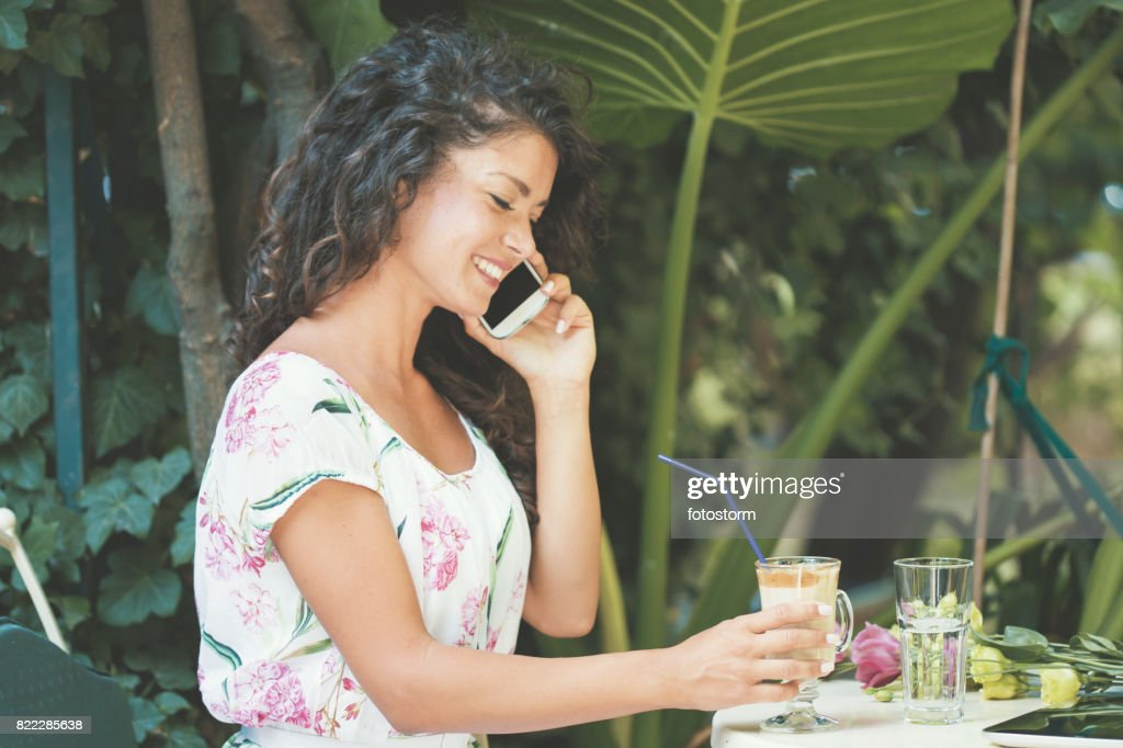 Woman using cell phone in sunny garden : Stock Photo