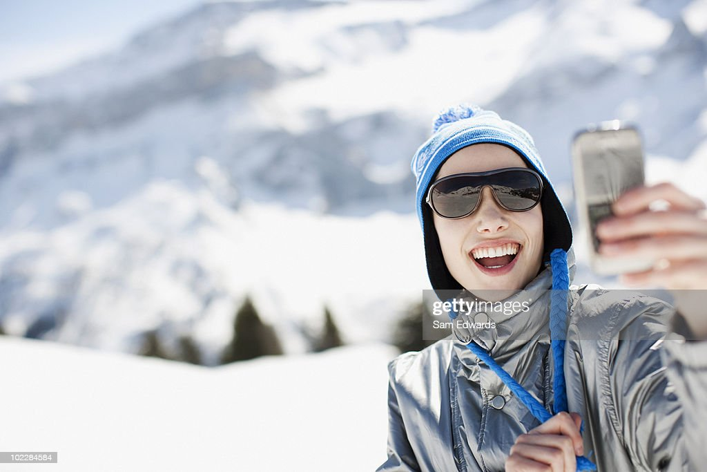 Woman using cell phone outdoors in snow : Stock Photo