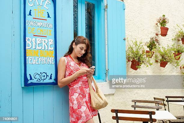 Woman using cell phone outside cafe