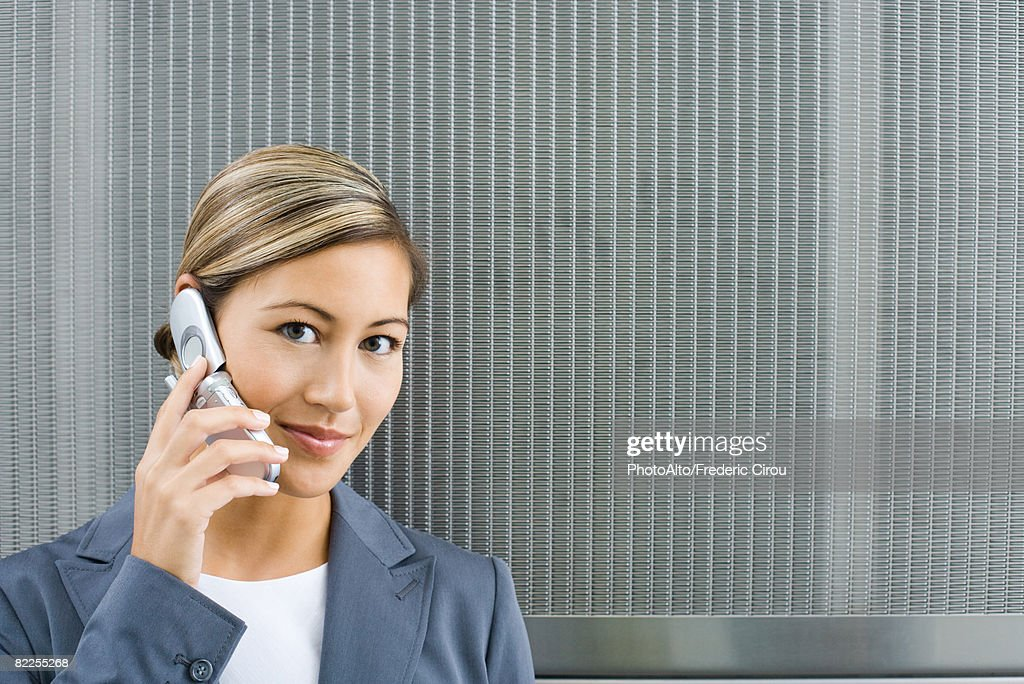 Woman using cell phone, smiling at camera : Stock Photo