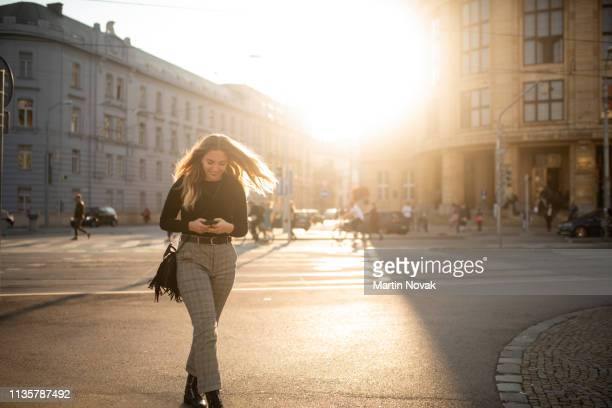 woman using cell phone while crossing road - busy sidewalk stock pictures, royalty-free photos & images